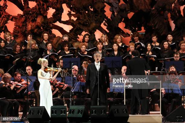 Italian tenor and singersongwriter Andrea Bocelli flanked by violinist Anastasiya Petryshak performs at the Paul VI Hall for a benefit concert for...