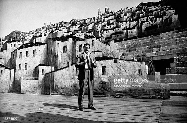 Italian tenor Franco Corelli, born Dario Corelli, poses in ordinary clothes on the Verona Arena stage, in front of the little white houses...