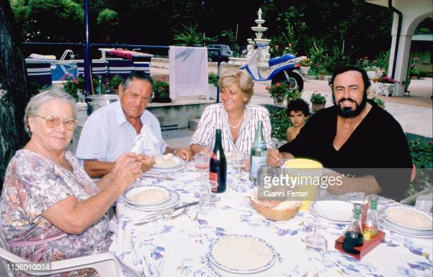 Italian tenor Luciano Pavarotti sits with from left his parents Adele and Fernando Pavarotti and wife Adua Pavarotti as they dine outdoors at his...