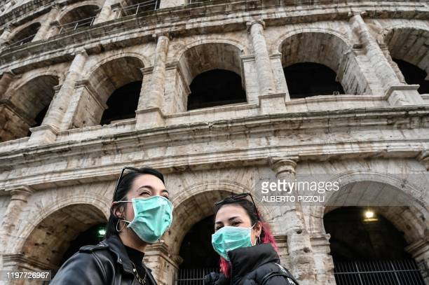 Italian tourists Alessia and Noemi from Cagliari, Sardinia, wearing a protective respiratory mask, tour outside the Colosseo monument during holidays...