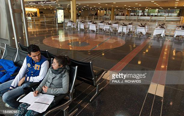 Italian tourists Patrizio D'Emido and his girlfriend Joelle Carota sit in the closed Ronald Reagan National Airport stranded between flights with a...