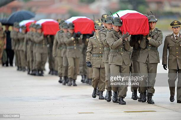 Italian troops carry on October 11 2010 the coffins of four soldiers killed on October 9 in Afghanistan at Ciampino military airport in Rome Four...