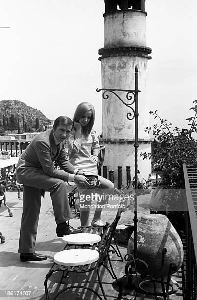 Italian TV and radio presenter Mike Bongiorno and his partner the Italian journalist and art director Annarita Torsello resting one foot on a bench...