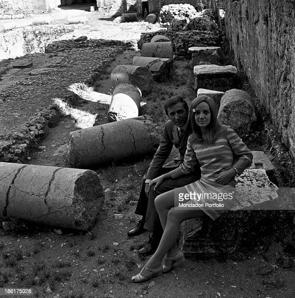 Italian TV and radio presenter Mike Bongiorno and his partner the Italian journalist and art director Annarita Torsello sitting at the Ancient...