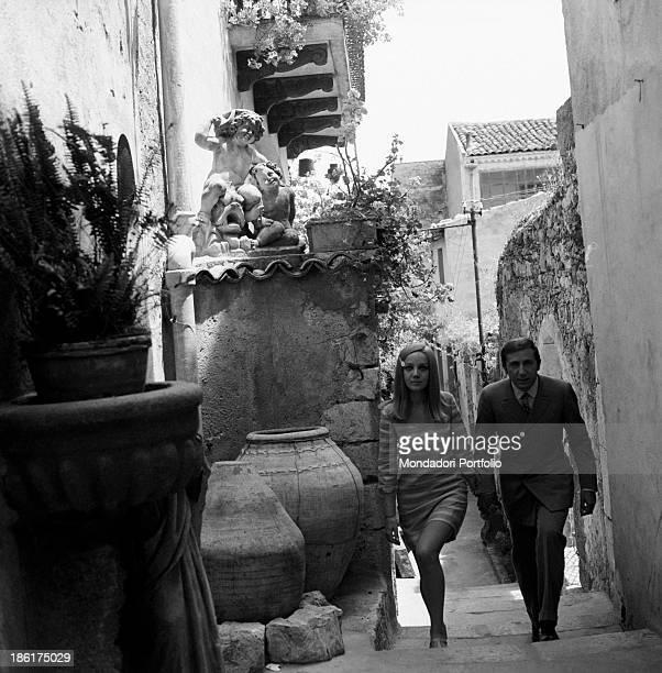 Italian TV and radio presenter Mike Bongiorno and his partner the Italian journalist and art director Annarita Torsello walking hand in hand Taormina...