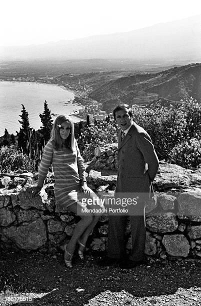 Italian TV and radio presenter Mike Bongiorno and his partner the Italian journalist and art director Annarita Torsello standing near a stone wall...