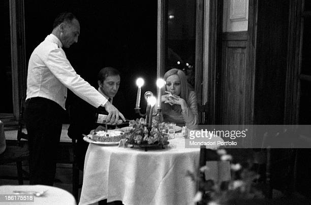 Italian TV and radio presenter Mike Bongiorno and his partner the Italian journalist and art director Annarita Torsello sitting at the table in a...