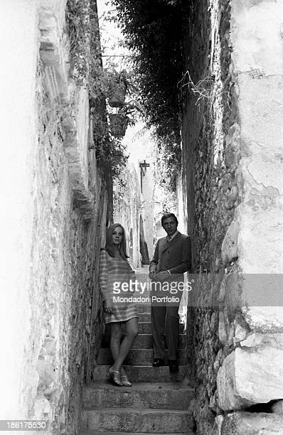 Italian TV and radio presenter Mike Bongiorno and his partner the Italian journalist and art director Annarita Torsello standing on the steps of a...