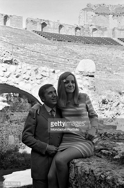 Italian TV and radio presenter Mike Bongiorno hugging his partner the Italian journalist and art director Annarita Torsello sitting on a low wall at...