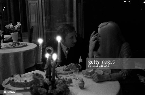 Italian TV and radio presenter Mike Bongiorno talking to his partner the Italian journalist and art director Annarita Torsello The couple is sitting...