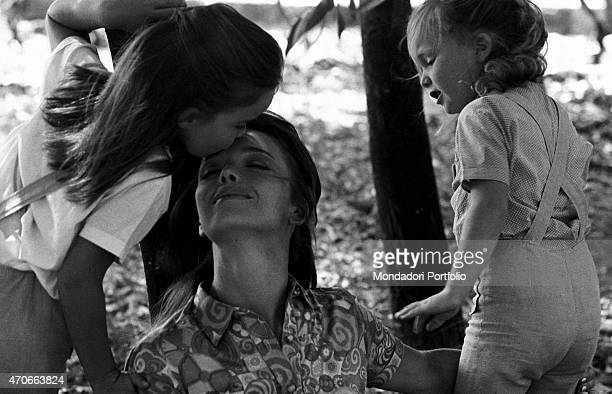 'Italian TV announcer Aba Cercato plays with her two little daughters Giulia and Francesca into a garden near their home the older one Giulia kisses...