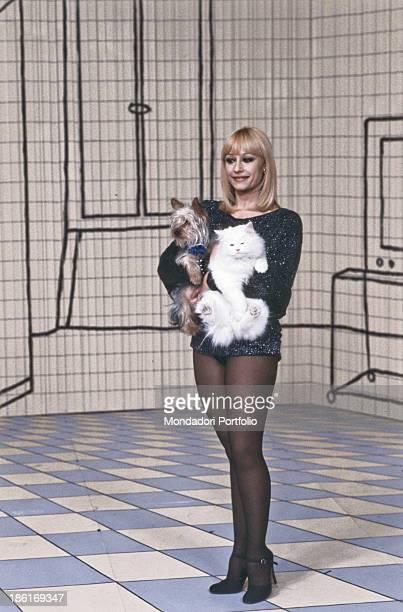 Italian TV host actress singer and showgirl Raffaella Carrà holding a cat and a dog while recording the theme song of the TV show Pronto Raffaella...