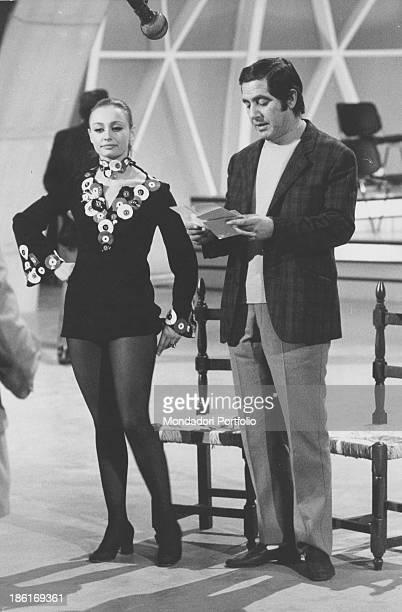 Italian TV host actress singer and showgirl Raffaella Carrà listening to Italian TV and radio author and host Corrado reading in the TV music show...