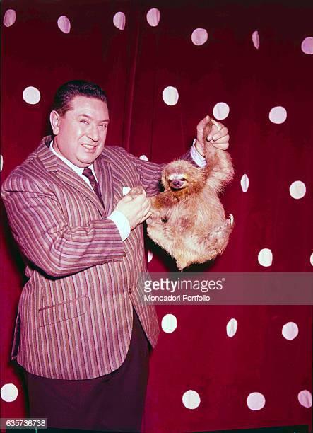 Italian TV host Angelo Lombardi holding a sloth in the TV show L'amico degli animali 1960