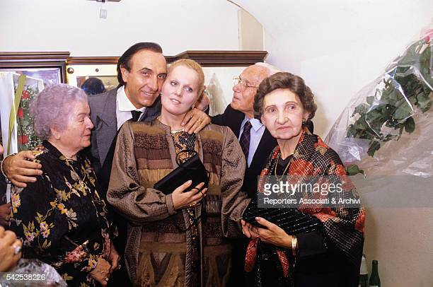 Italian TV host Pippo Baudo hugging his second wife Katia Ricciarelli , famous Italian soprano, in the dressing room after her successful concert....
