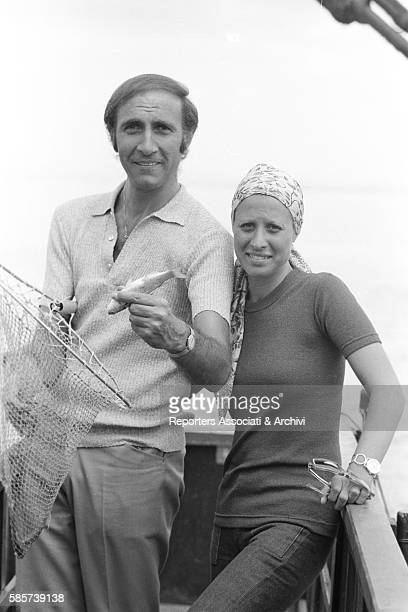 Italian TV host Pippo Baudo on holiday with his first wife Angela Lippi on a Roman coast beach In the picture the TV host shows a net with some fish...
