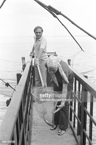 Italian TV host Pippo Baudo on holiday with his first wife Angela Lippi on a Roman coast beach In the picture the TV host on a jetty presenting a net...