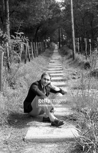 Italian TV host Pippo Baudo sitting on a flight of steps 1967