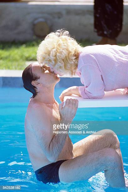 Italian TV host Pippo Baudo softly kissing his wife Katia Ricciarelli , Italian soprano and actress, while swimming in a pool. Italy, 1986