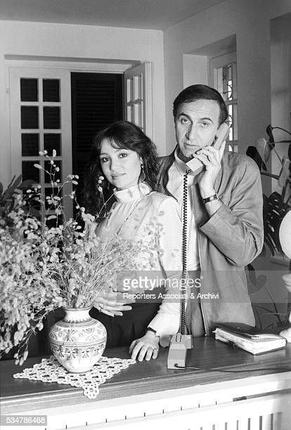 Italian TV host Pippo Baudo speaking over the phone beside his partner and Italian actress Adriana Russo at home 1981