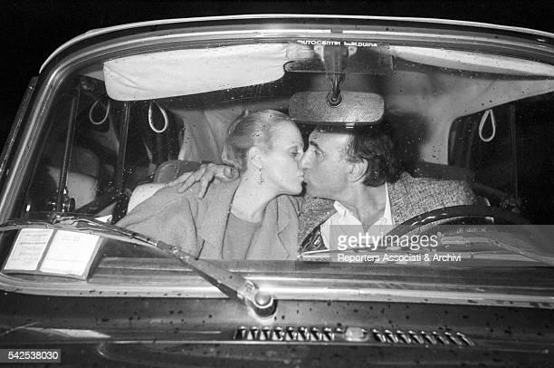 Italian TV host Pippo Baudo with Katia Ricciarelli , his fiancée and famous Italian soprano, kissing in a car. Italy, 1983