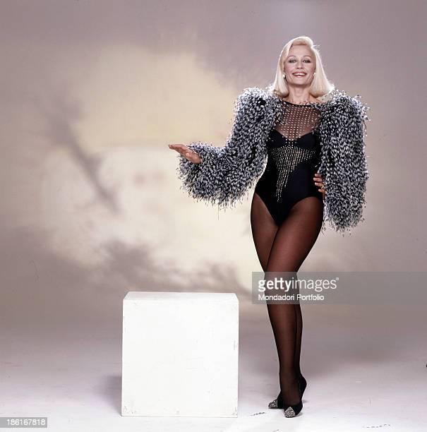 Italian TV presenter actress singer and showgirl Raffaella Carrà wearing a leotard with feathers sleeves designed by Italian fashion designer Rocco...