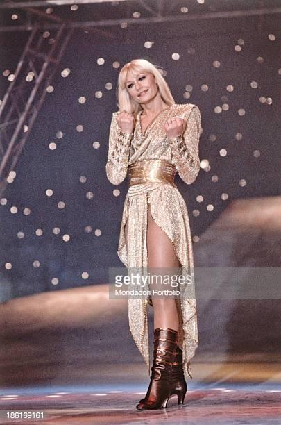 Italian TV presenter actress singer and showgirl Raffaella Carrà wearing a golden dress in the TV variety show Buonasera Raffaella Italy 1985