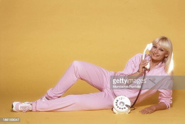 Italian TV presenter actress singer and showgirl Raffaella Carrà lying wearing a pink tracksuit with a receiver in her right hand 1984