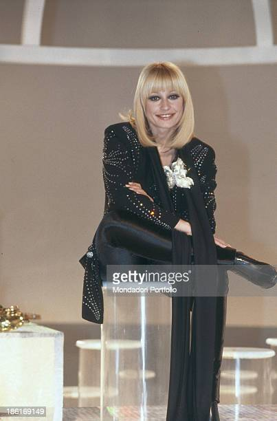 Italian TV presenter actress singer and showgirl Raffaella Carrà sitting on a stool in the studio of the TV music show Millemilioni Italy 1981