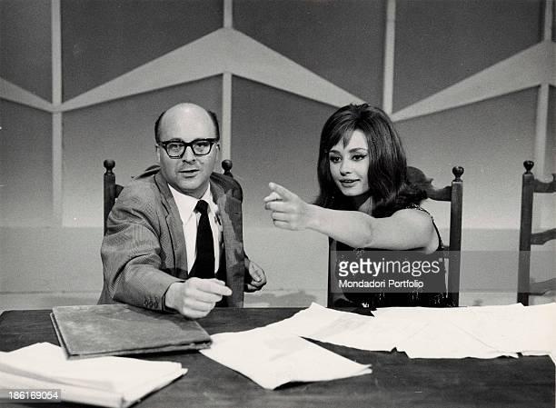 Italian TV presenter actress singer and showgirl Raffaella Carrà sitting beside Italian director Lino Procacci in the TV show Il paroliere questo...