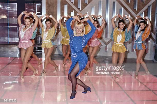 Italian TV presenter actress singer and showgirl Raffaella Carrà dancing with some dancers in the TV variety show Buonasera Raffaella Italy 1985