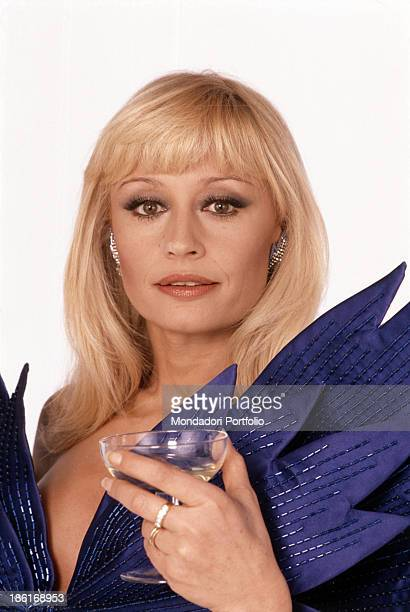 Italian TV presenter actress singer and showgirl Raffella Carrà looking into the camera holding a goblet in her left hand 1984