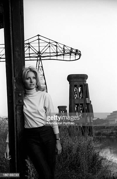 Italian TV presenter and actress Gabriella Farinon posing leaning against a pylon Italy 1968
