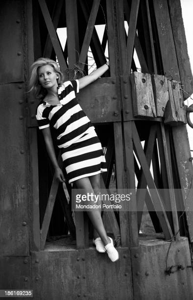 Italian TV presenter and actress Gabriella Farinon posing leaning on a pylon Italy 1968