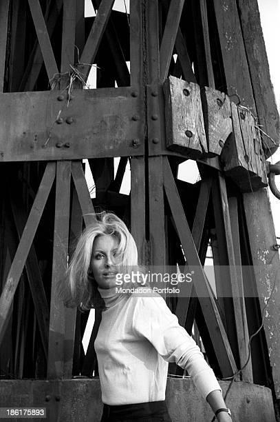 Italian TV presenter and actress Gabriella Farinon posing near a pylon Italy 1968