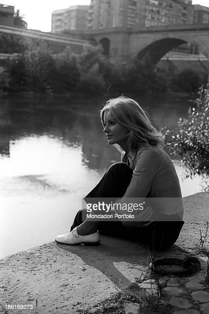 Italian TV presenter and actress Gabriella Farinon sitting on a river bank Italy 1968