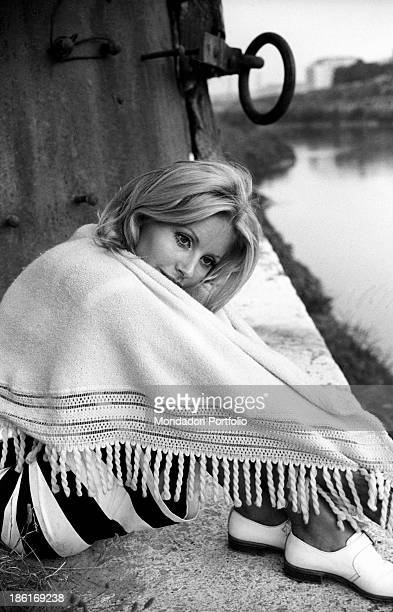 Italian TV presenter and actress Gabriella Farinon sitting wrapped up in a shawl on a river bank Italy 1968