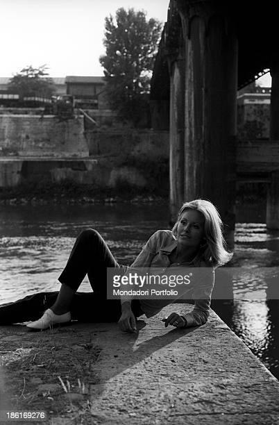 Italian TV presenter and actress Gabriella Farinon smiling lying on a river bank Italy 1968