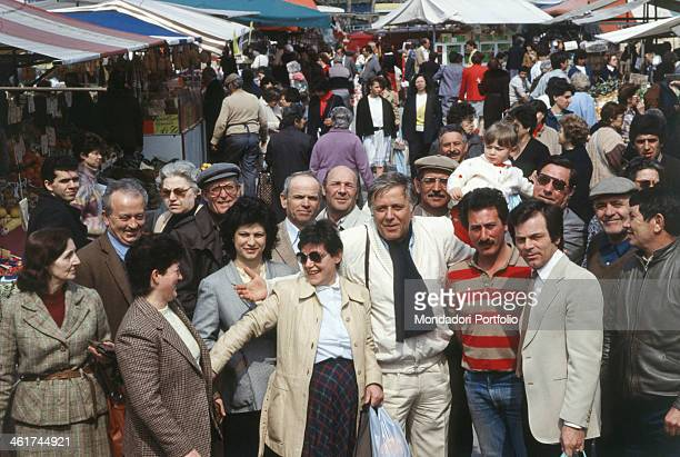 Italian TV presenter Gianfranco Funari in an open air market calling some people for a group photograph Italy 1985