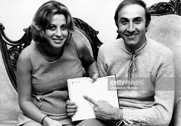 Italian TV presenter Pippo Baudo and his wife Angela Lippi pointing at the 7th December on a diary Milan 1970