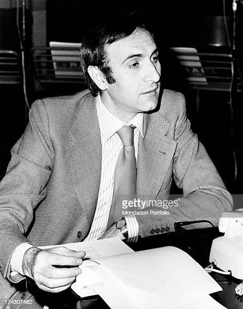 Italian TV presenter Pippo Baudo sitting and leafing through a script. Milan, 1973.