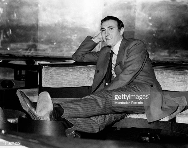 Italian TV presenter Pippo Baudo sitting on a sofa with his legs on a pouf January 1968