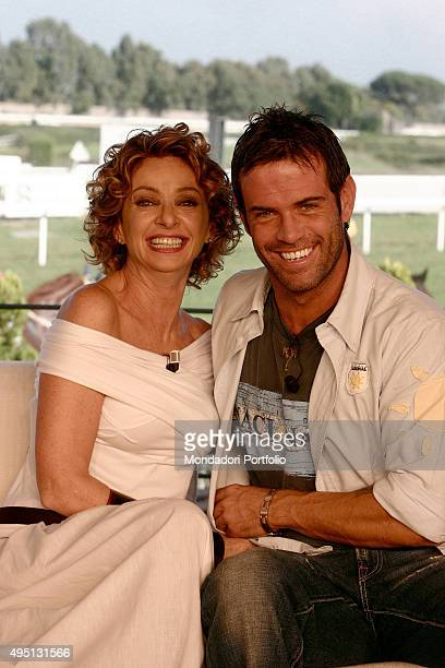 Italian Tv presenters Enrica Bonaccorti and Ascanio Pacelli posing smiling for a photo shooting shooted in the TV studio of the show 'Il mio migliore...