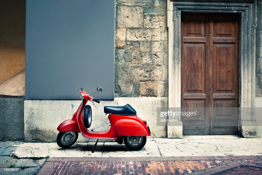 Italian vintage red scooter in front of a house : Stock Photo