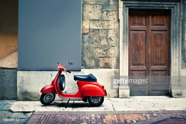Italian vintage red scooter in front of a house