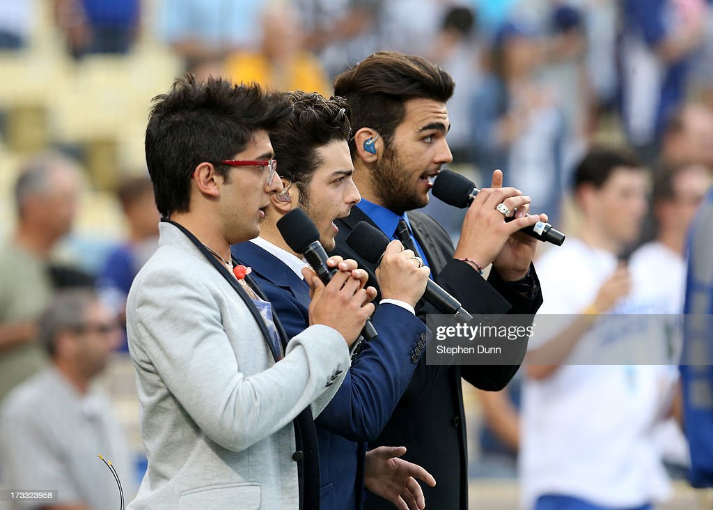 Italian vocal group Il Volo (L to R) Piero Barone, Gianluca Ginoble and Ignazio Boschetto sing the US national anthem before the game between the Colorado Rockies and the Los Angeles Dodgers at Dodger Stadium on July 11, 2013 in Los Angeles, California.