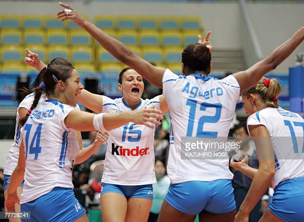 Italian volleyball players cheer up each other after scoring against Serbia at the women's World Cup volleyball tournament at the Namihaya Dome in...