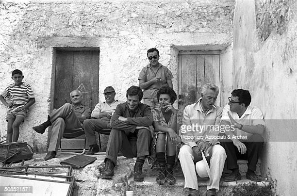Italian writer Alberto Moravia and producer Carlo Ponti visit with Italian actress Sophia Loren French actor Jean Paul Belmondo director Vittorio de...