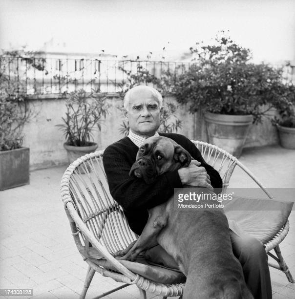 Italian writer Alberto Moravia hugging a dog on a terrace 1960s