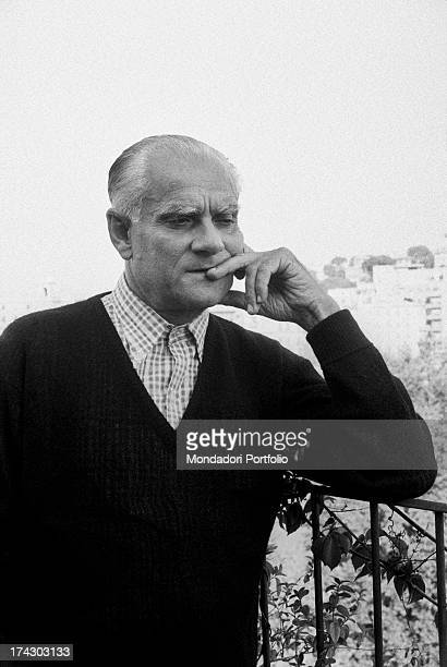 Italian writer Alberto Moravia leaning on the rail of a terrace 1960s